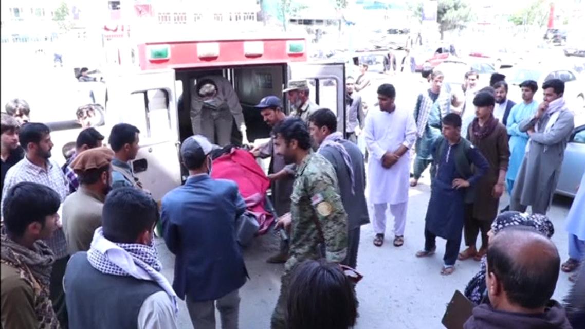 Men putting body bag containing dead ex-journalist into ambulance outside Kabul hospital. (Photo courtesy: Radio Free Europe via Reuters)