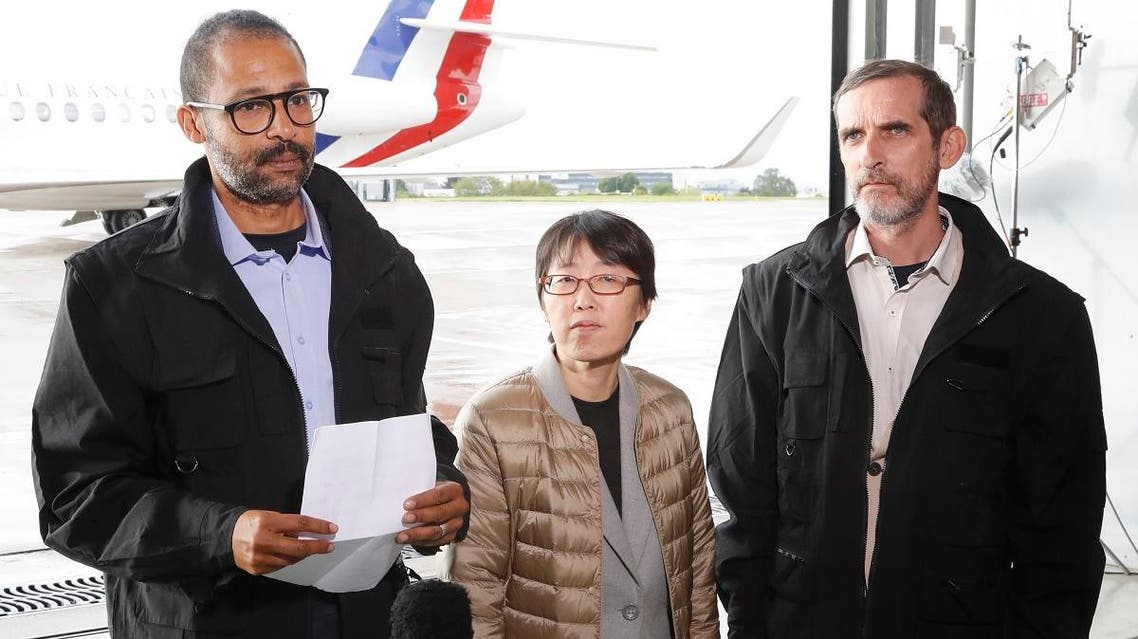 Freed French hostages Patrick Picque (R) and Laurent Lassimouillas (L) stand next to a South Korean hostage who has not been identified yet, as they talk to the press upon their arrival at the Villacoublay airport, near Paris, on May 11, 2019. (AFP)