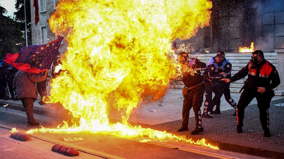 Albanian policemen try to avoid the flames from a petrol bomb during an anti-government protest called by the opposition. (AFP)