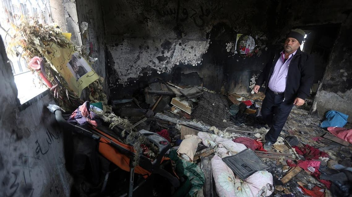 A relative stands on January 3, 2016, inside the burnt-out home of Saad Dawabsha, who was killed alongside his toddler and his wife when their house was firebombed by Jewish extremists on July 31, 2015, in the West Bank village of Duma. (AFP)