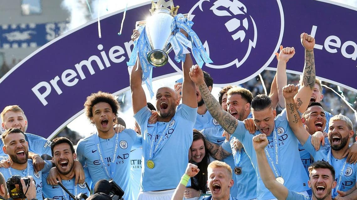 Manchester City's Vincent Kompany lifts the trophy as they celebrate winning the Premier League. (Reuters)