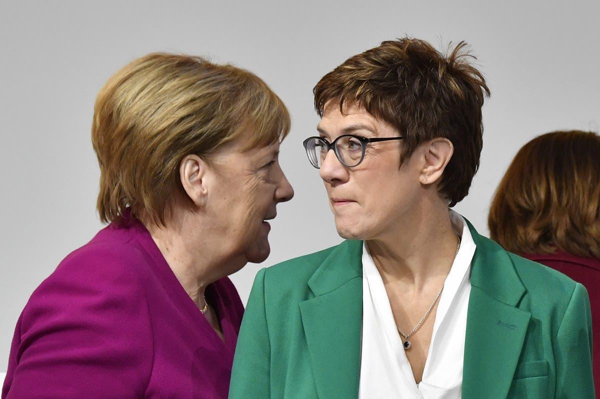 German Chancellor Angela Merkel (L) walks past her successor, newly- elected leader of Germany's conservative Christian Democratic Union (CDU) party Annegret Kramp-Karrenbauer. (AFP)