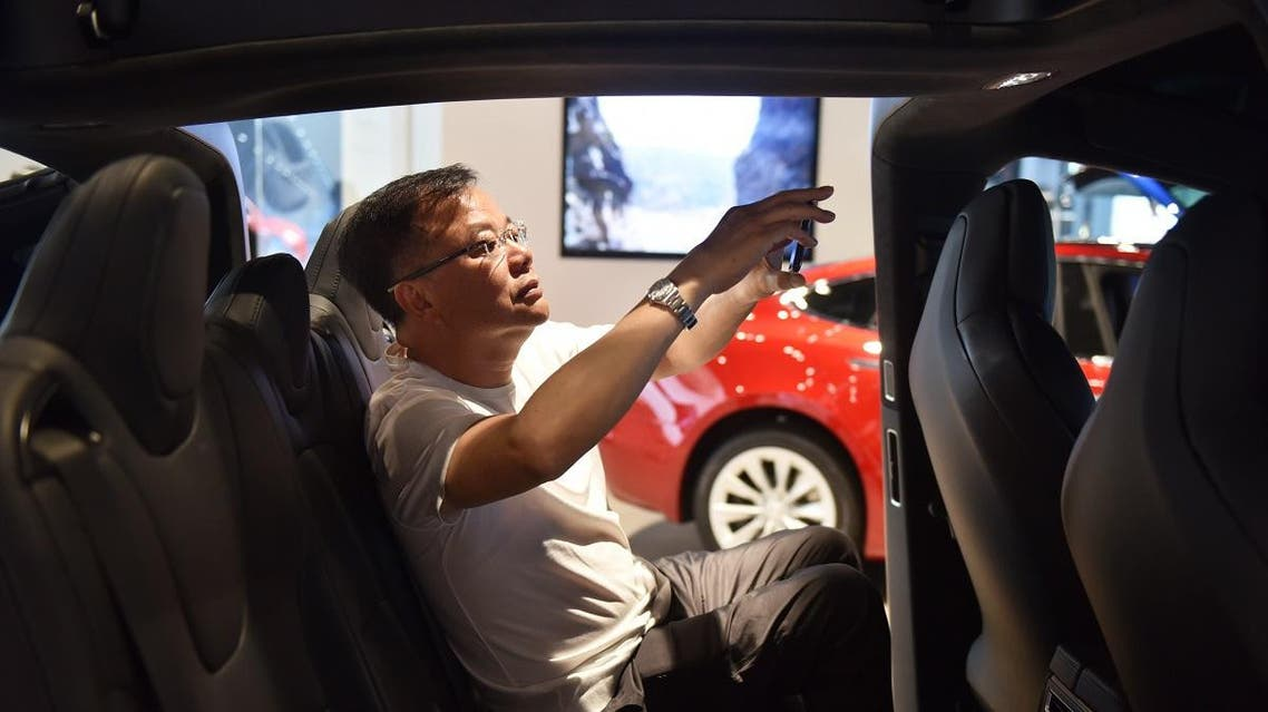 A man takes a photo inside a Tesla Model X in a Tesla showroom in Beijing. (AFP)