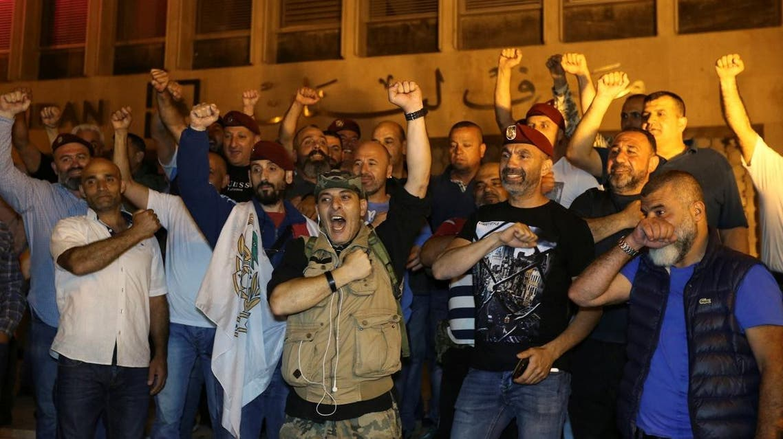 Retired soldiers gesture as they take part in a protest over proposed cuts to the cost of military pensions and benefits in front of the central bank in Beirut. (Reuters)