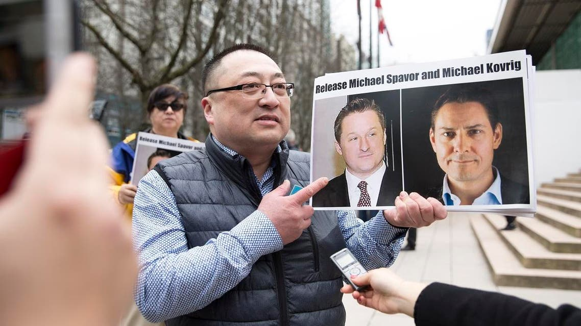 Louis Huang of Vancouver Freedom and Democracy for China holding photos of Canadians Michael Spavor and Michael Kovrig, who are being detained by China, outside British Columbia Supreme Court, in Vancouver. (AFP)