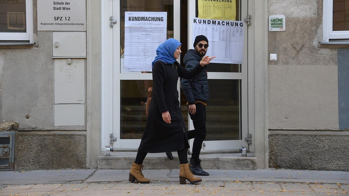 A woman wearing a headscarf and a man leave a polling station during general elections in Vienna on October 15, 2017. (AFP)
