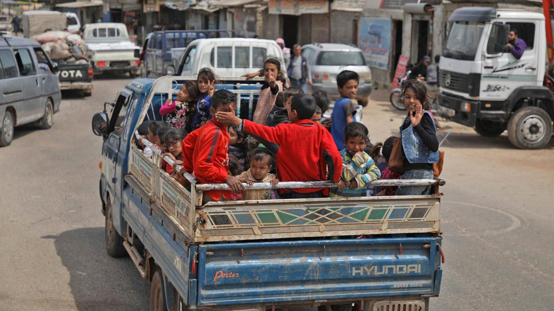 Syrian children, riding on the back of a truck, flee from shelling on Hama and Idlib provinces on May 1, 2019. (AFP)