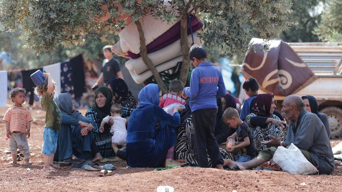 Displaced Syrians sit together in an olive grove in Atmeh town, Idlib province, Syria May 15, 2019. Picture taken May 15, 2019. (Reuters)