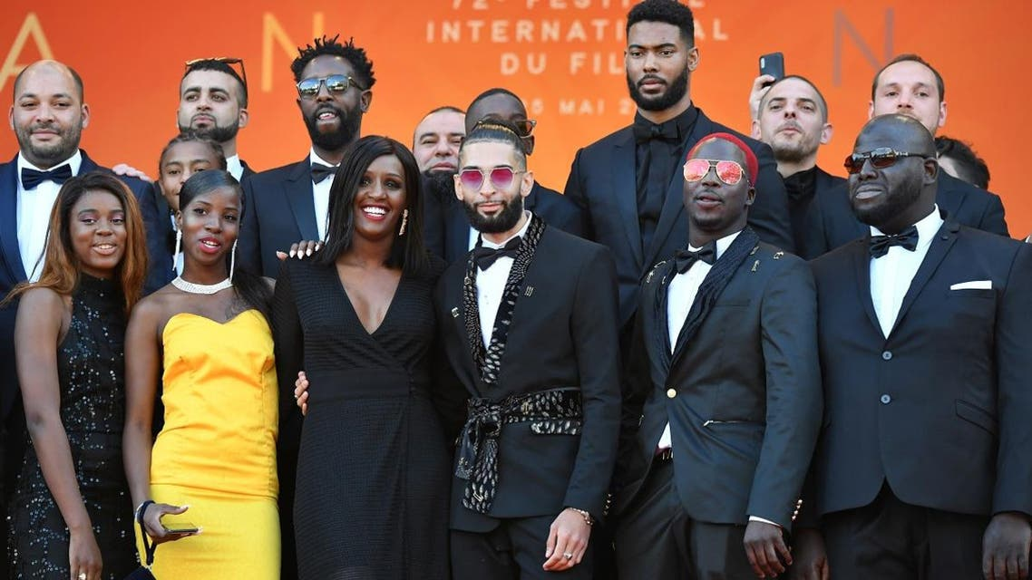 """French director Ladj Ly (6th left) poses with his cast as he arrives for the screening of his film """"Les Miserables"""" at the 72nd edition of the Cannes Film Festival in Cannes, southern France, on May 15, 2019. (AFP)"""