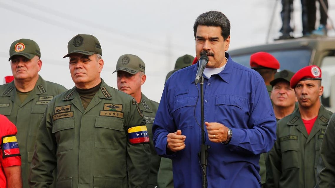 Handout photo released by Miraflores Palace press office showing Venezuela's President Nicolas Maduro (C) and Defense Minister Vladimir Padrino (C-R) raising their arms during the march of loyalty with the Superior Staff of the Venezuela's Bolivarian National Armed Forces (FANB) and all military personnel stationed in the ZODI Aragua state, Venezuela on May 17, 2019. (AFP)