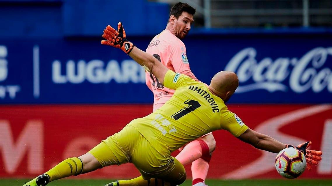 Barcelona's Messi shoots to score in front Eibar's goalkeeper Marko Dmitrovic during a Spanish La Liga match in Eibar, northern Spain, Sunday, May 19, 2019. (AP)