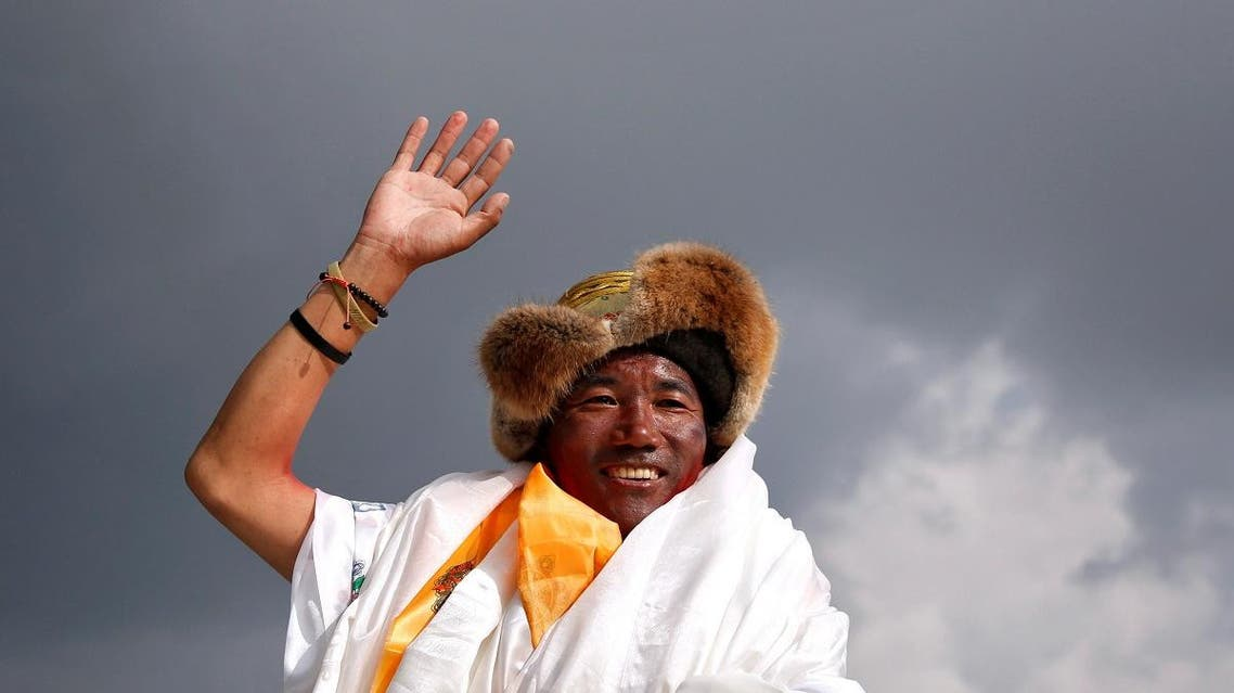 Kami Rita Sherpar waves towards the media personnel upon his arrival after climbing Mount Everest for a 22nd time, creating a new record for the most summits of the world's highest mountain, in Kathmandu May 20, 2018. (Reuters)