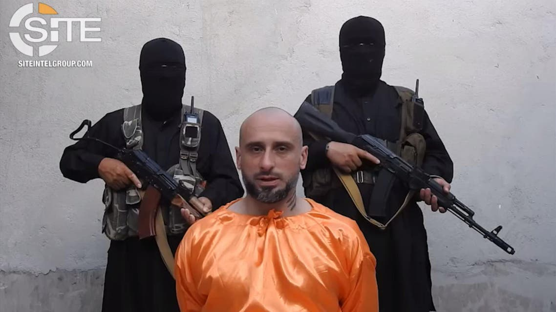 This video image released on July 31, 2018, and provided courtesy of SITE Intelligence Group, shows Alessandro Sandrini appealing for his release as two armed men stand behind him at an unknown location in Syria. (AFP)