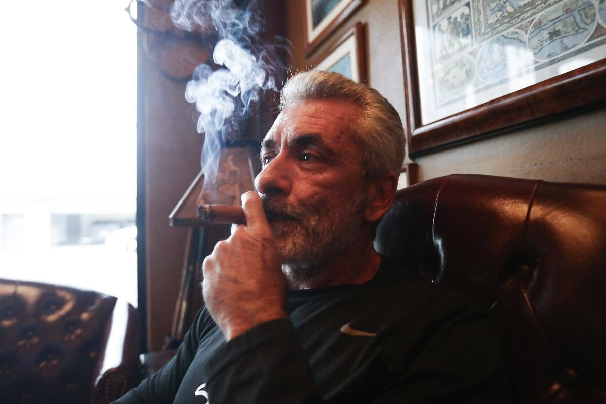 Owner Rigo Fernandez poses for photos smoking a cigar in his Buena Vista Cigar Club on May 10, 2019 in Beverly Hills, California. (AFP)