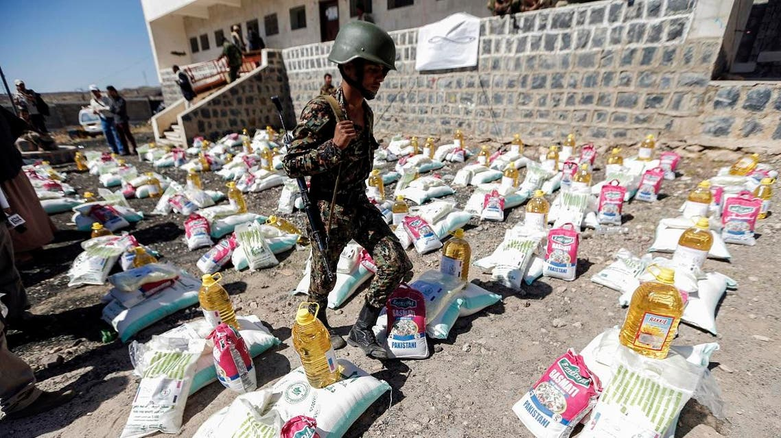 A Yemeni Houthi walks next to humanitarian aid supplies in a camp on the outskirts of the capital Sanaa on March 16, 2017. (AFP)