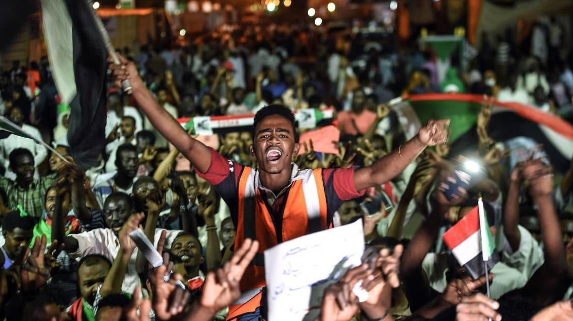 Sudanese protesters wave flags and flash victory signs as they gather for a sit-in outside the military headquarters in Khartoum. (AFP)