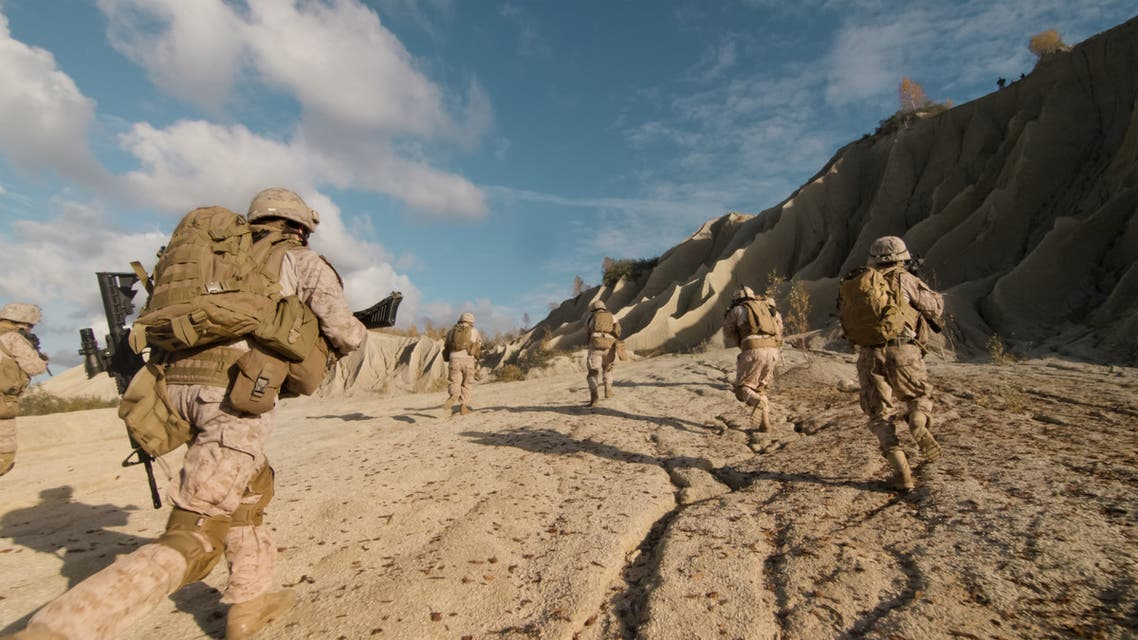 Shot of a Squad of Soldiers Running Forward and Atacking Enemy During Military Operation in the Desert. - Stock image