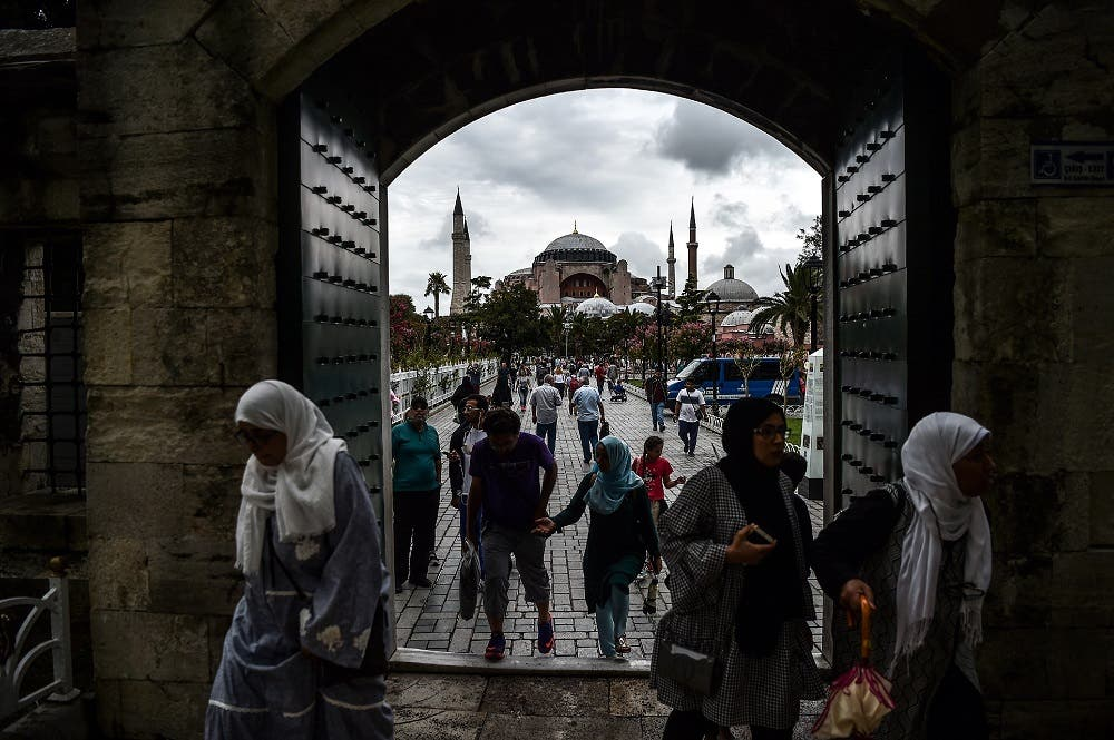 People enter to Sultanahmet (Blue) mosque on August 22, 2017 near the Hagia Sophia (in the background) during a rainy day in Istanbul. (AFP)