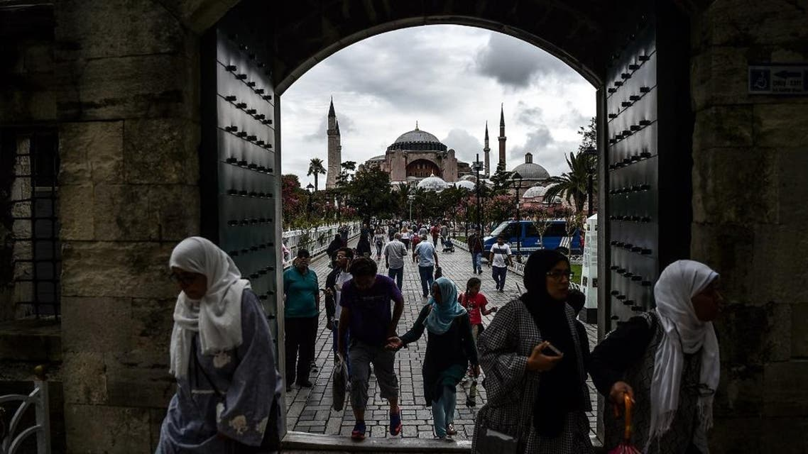 People enter to Sultanahmet (Blue) mosque on August 22, 2017 near the Hagia Sophia (in the background) during a rainy day in Istanbul. afp