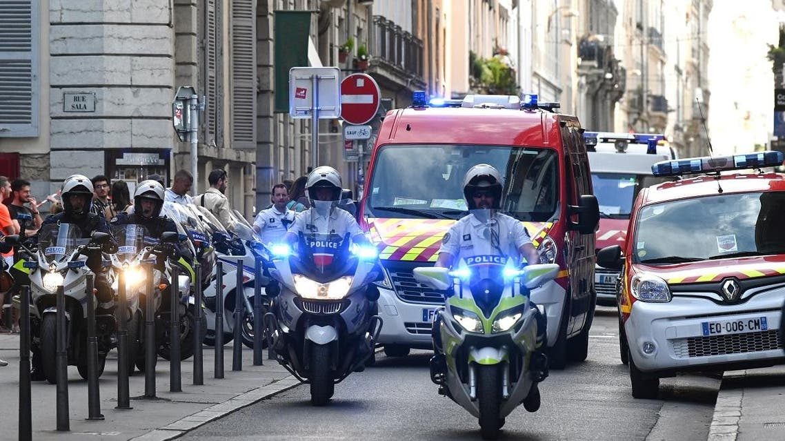 French police escort the emergency services following a suspected package bomb blast along a pedestrian street in the heart of Lyon, southeast France, on May 24, 2019. (AFP)