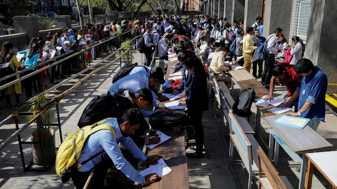 Job seekers fill up forms as others line up for registration during a job fair in Chinchwad, India, on February 7, 2019. (Reuters)