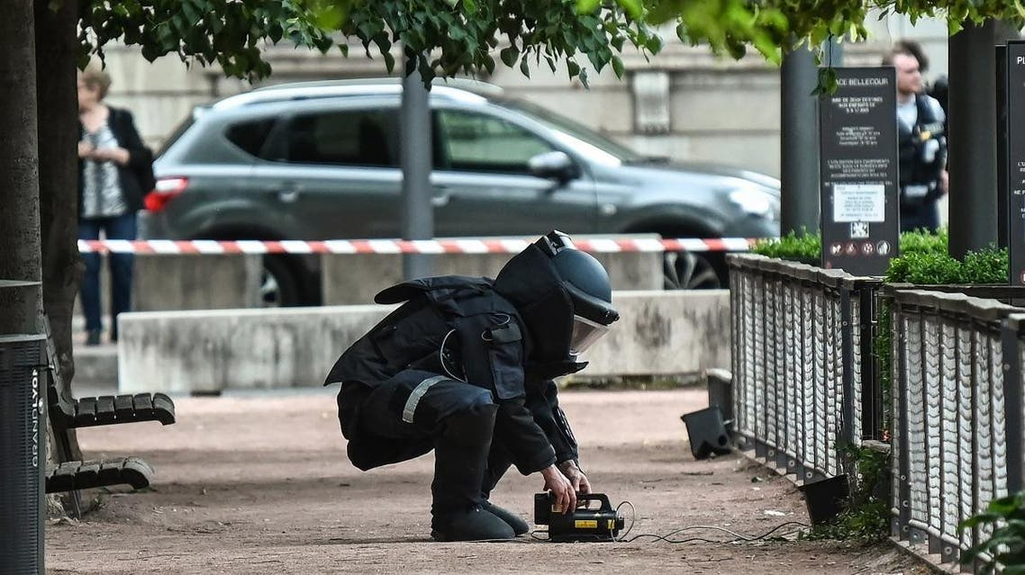 A bomb disposal expert works at the scene of a suspected package bomb blast along a pedestrian street in the heart of Lyon, southeast France, on May 24, 2019.