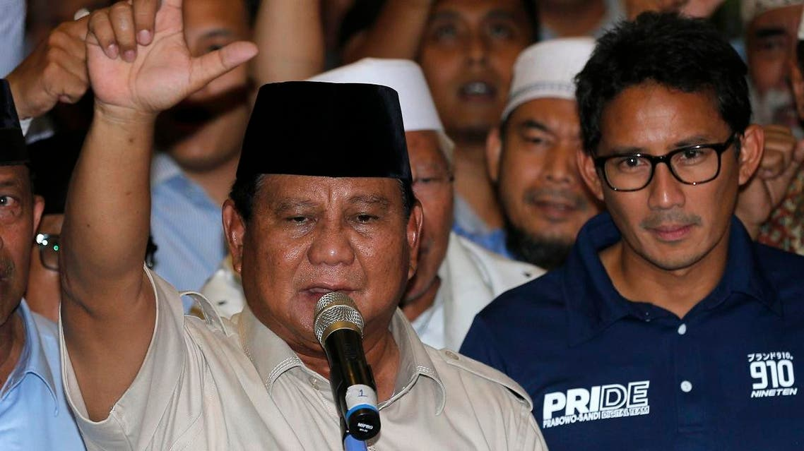 Indonesian presidential candidate Prabowo Subianto, left, raises his hands as his running mate Sandiaga Uno looks on during a speech declaring their victory in April 17 election in Jakarta, Indonesia, Thursday, April 18, 2019. (AP)