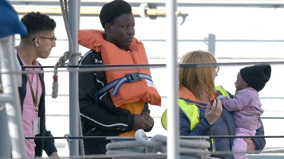 A woman (C) and a child (R) with the migrants who were stuck on a ship since their rescue in the Mediterranean 10 days ago, are being welcomed after disembarking in Valletta, Malta, on April 13, 2019 after four European countries agreed to take the migrants in. (AFP)