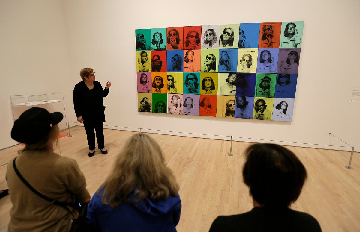 "Donna DeSalvo, deputy director and senior curator at New York's Whitney Museum of American Art, talks about the piece ""Ethel Scull 36 Times"" displayed in the exhibition ""Andy Warhol - From A to B and Back Again,"" in San Francisco. (AP)"