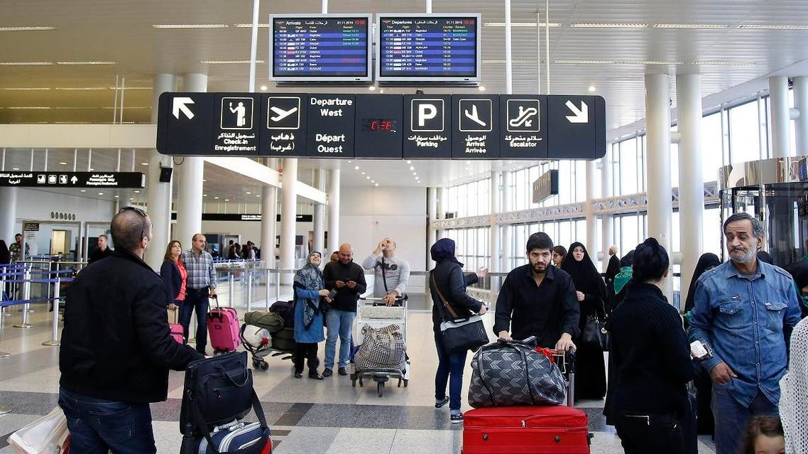 Travelers check the flight schedule screens for delays or cancellations, at the departure terminal of Rafik Hariri international airport in the Lebanese capital, Beirut. (AFP)