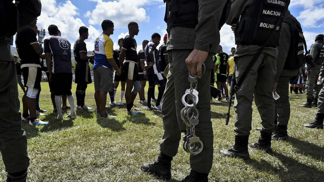 A member of the Bolivarian National Guard holds handcuffs after taking them off from inmates of a rugby team during the Penitentiary Rugby Tournament organized by the Santa Teresa Foundation, at the sports field Hacienda Santa Teresa in La Victoria, Aragua State, Venezuela, on December 1, 2018. (AFP)
