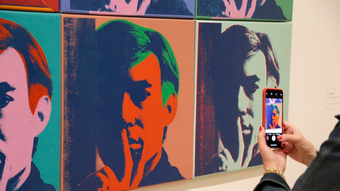 """A woman records one of a series of self portraits at the exhibition, """"Andy Warhol - From A to B and Back Again,"""" in San Francisco. (AP)"""