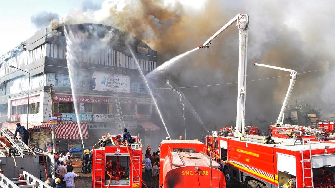 Indian firefighters try to control a major fire in a building housing a college, in Surat, some 270 kms. from Ahmedabad on May 24, 2019. (AFP)