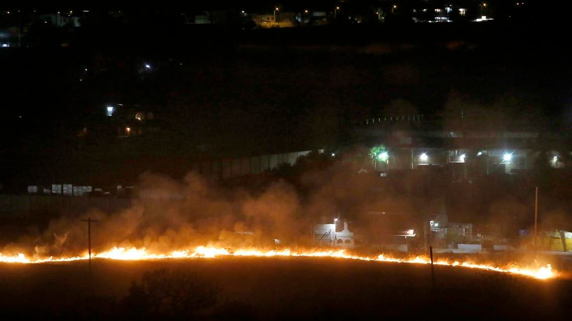 A line of fire running down a hill in La Primavera forest reaches the residential area of Pinar de la Venta in Zapopan, Jalisco State, Mexico, early on May 15, 2019. (AFP)