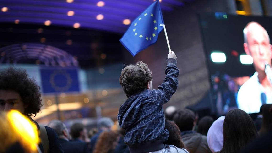 A young boy waves an EU flag as he watches a giant screen television outside the European Parliament in Brussels, Sunday, May 26, 2019. (AP)