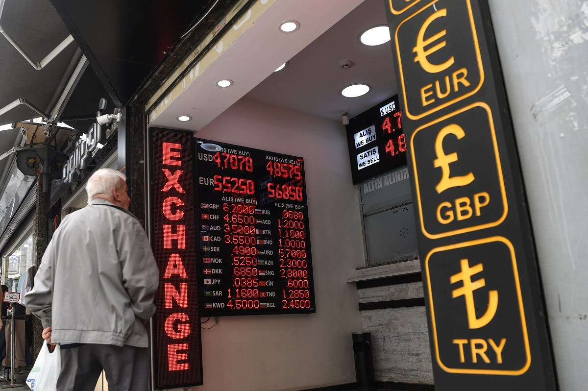 A man looks to a board displaying US dollars and Euros exchange rates in Turkish liras at an exchange office in Istanbul. (AFP)