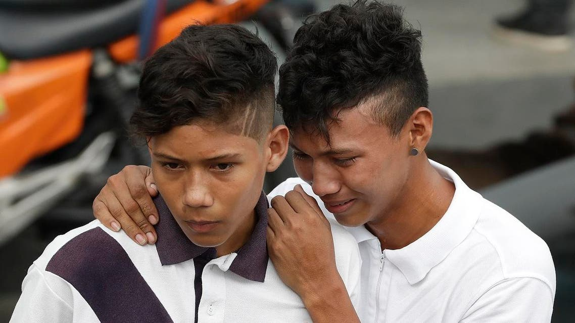 Two young men wait outside a morgue for the release of the body of their brother Gabriel Hilario de Jesus, an inmate who was killed in the recent prison riots, in Manaus, Brazil, Tuesday, May 28, 2019. (AP)