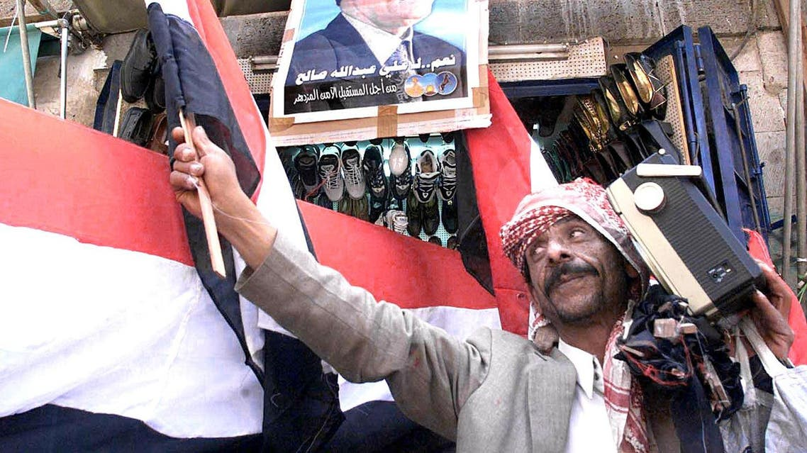 A Yemeni man listens to the radio as he sells the national flag in Sanaa on 19 September 1999. (File photo: AFP)