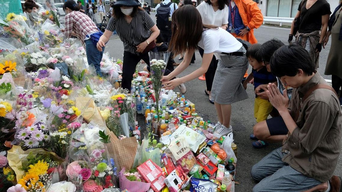 People pay their respects next to flower tributes at the crime scene where a man stabbed 19 people, including children, in Kawasaki on May 29, 2019. (AFP)