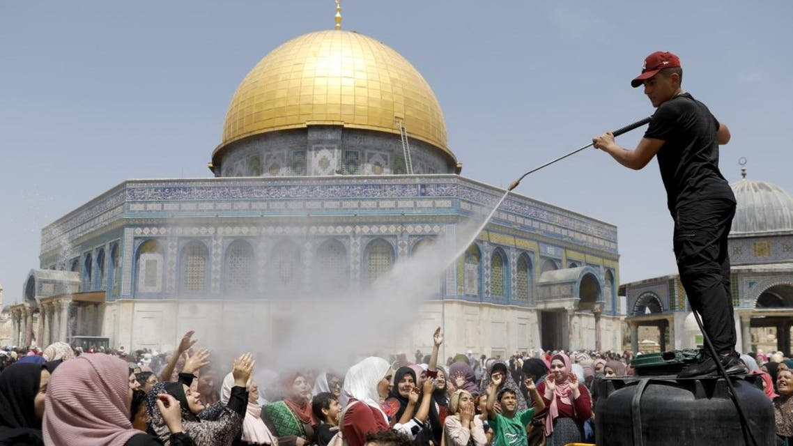 Women cool themselves down in a stream of water as Palestinians gather for the Friday prayer at Al Aqsa mosque during Al-Quds day in Jerusalem on May 31, 2019. (AFP)