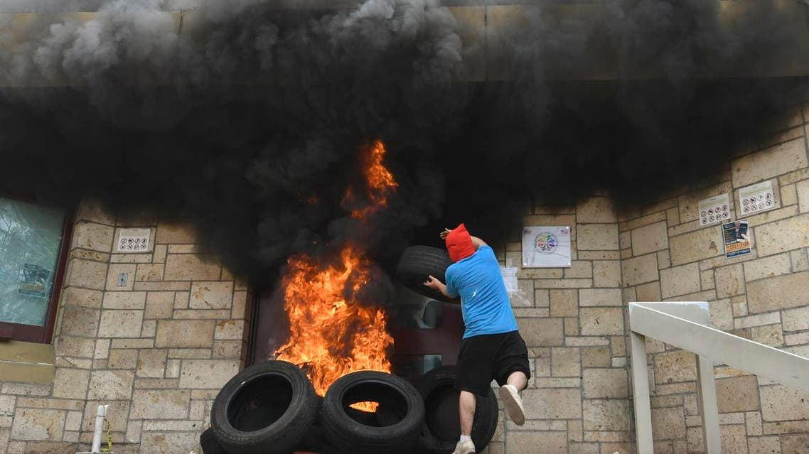 A masked demonstrator throws a tire into a burning fire at the entrance of the US embassy in Tegucigalpa during a demonstration of the education and health sectors protesting against government reforms, on May 31, 2019. (AFP)