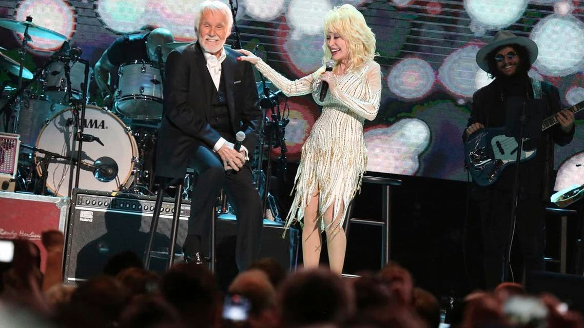 """Kenny Rogers (left), and Dolly Parton share a few stories at """"All In For The Gambler: Kenny Rogers' Farewell Concert Celebration"""" at Bridgestone Arena on Oct. 25, 2017, in Nashville, Tennessee. (AP)"""