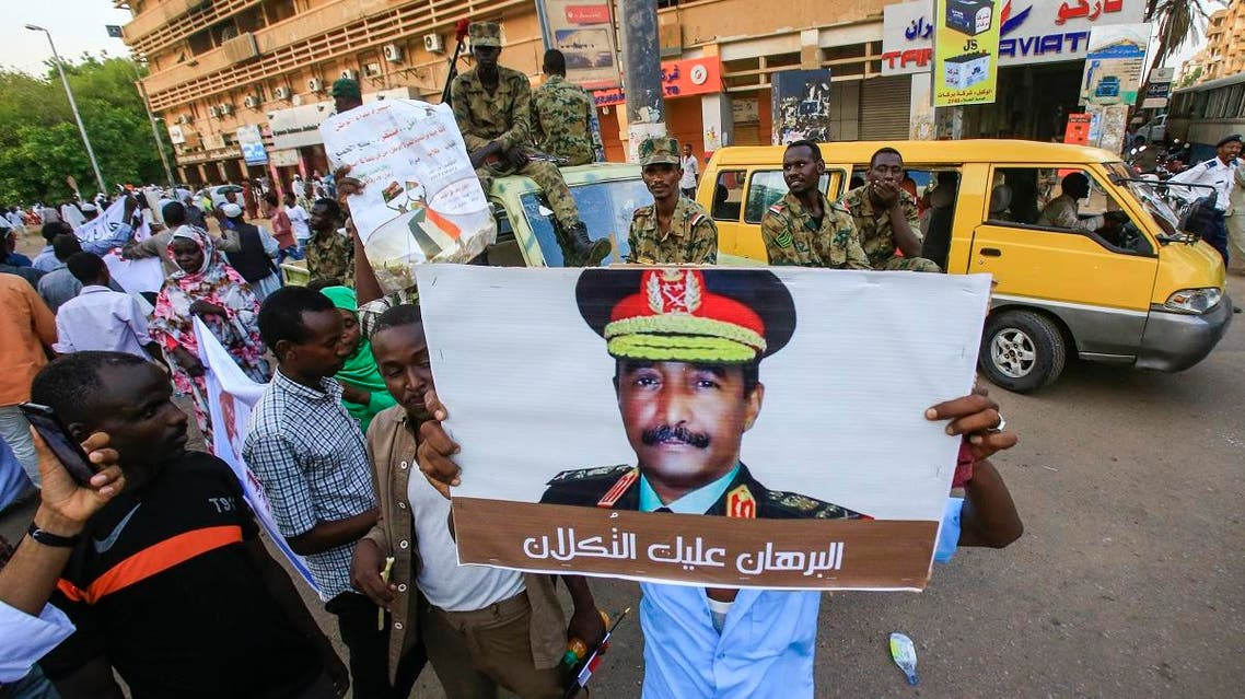 "Sudanese supporters of the ruling Transitional Military Council (TMC) hold up a sign showing a portrait of its head General Abdel Fattah al-Burhan with a caption below reading in Arabic ""Al-Burhan, upon you is the trust,"" during a rally in the center of the capital Khartoum on May 31, 2019. (AFP)"