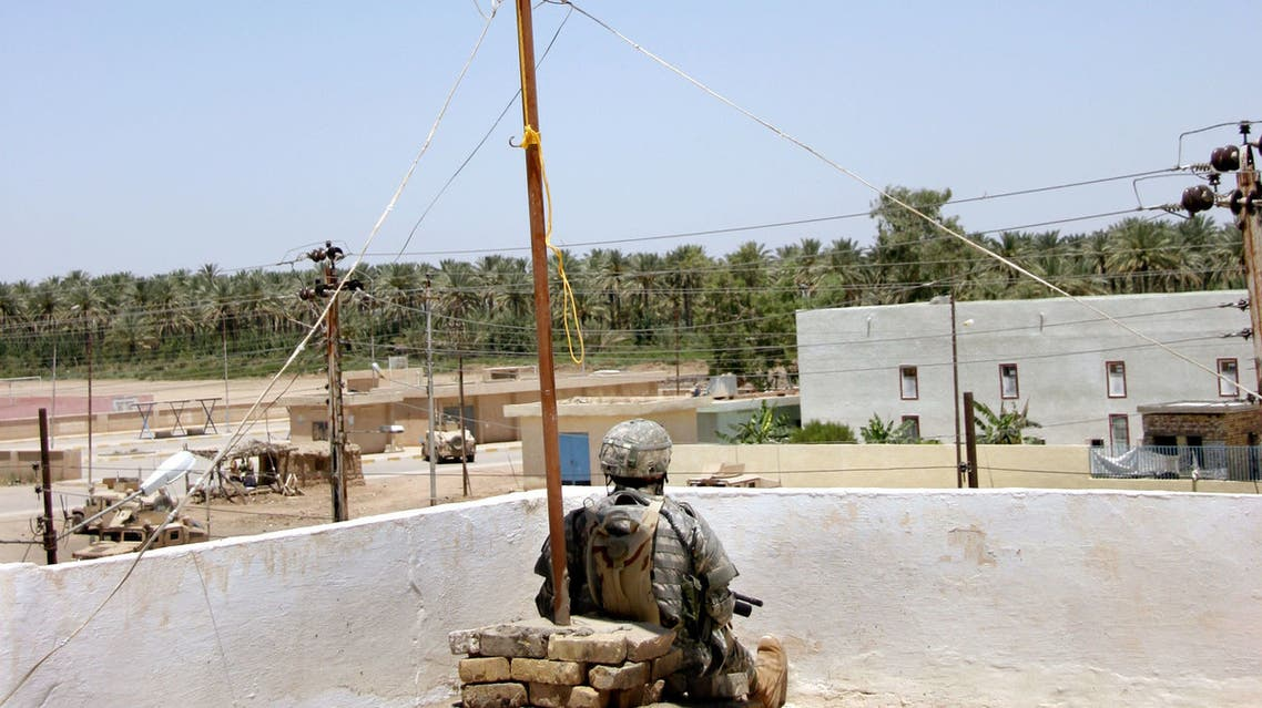 A US soldiers takes a break under an Iraqi flag on the roof on newly reconstructed police station in the Iraqi town of Tarmiyah, north of Baghdad, 25 May 2006. In the aftermath of the US-led invasion, Tarmiyah became known for little more than deadly roadside bombs and conservative Sunni sermons in its mosques. But now the largely Sunni town of 45,000 people, nestled amid endless date palms plantations on the edge of the Tigris just north of Baghdad, is being held up by the US military as a model in its efforts to secure and rebuild Iraq. AFP PHOTO/HO/US ARMY/SGT. TREVOR SNYDER