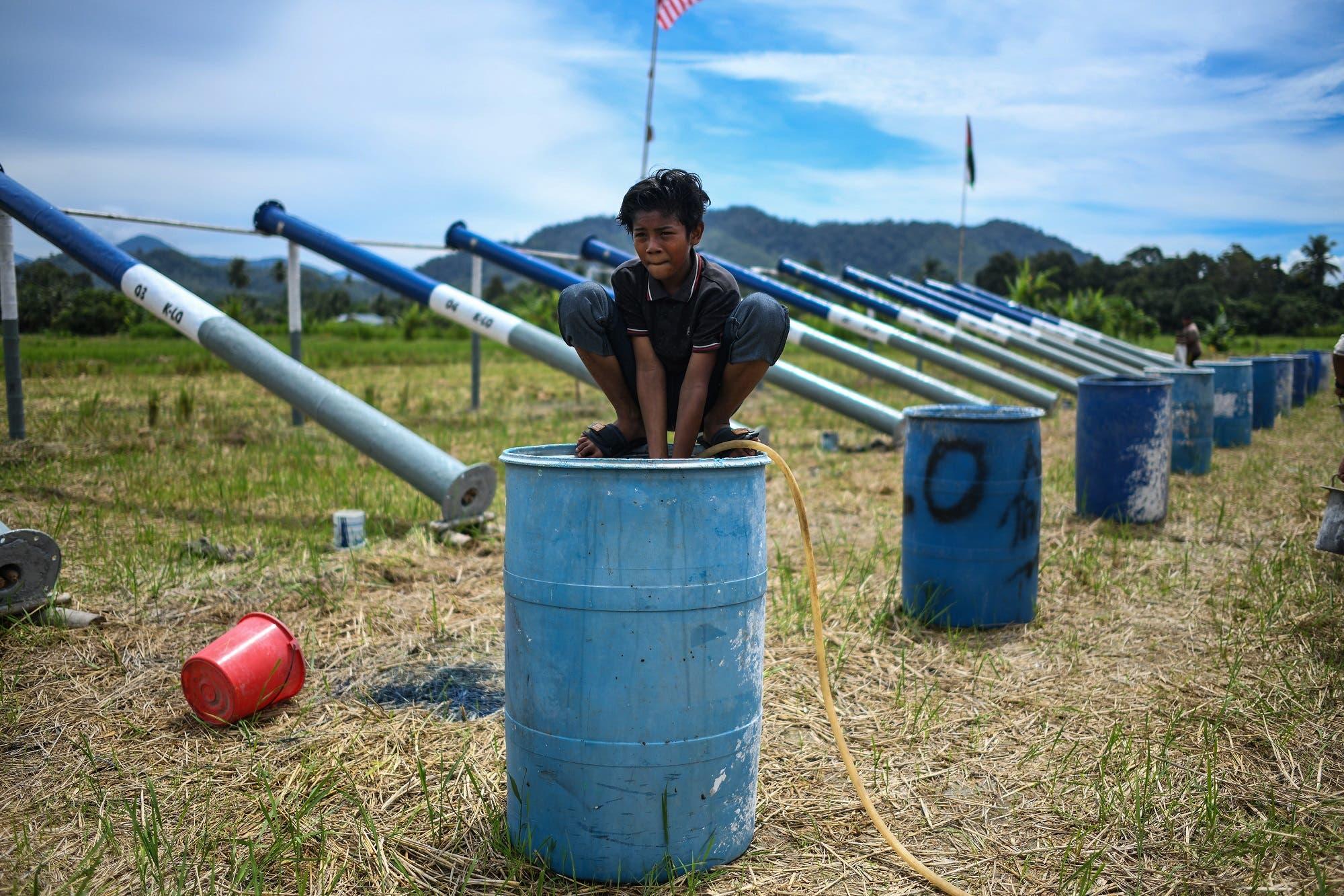 A boy filling water in a drum before firing steel cannons on the eve of Eid al-Fitr in Kuala Kangsar on June 4, 2019. (AFP)
