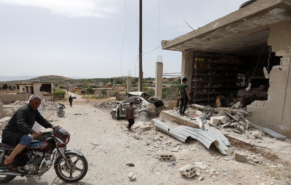 A man drives his motorcycle near a building that was damaged during an air strike by the Syrian government forces in town of Kafr Aweid, in the extremist-controlled region of Idlib on May 23, 2019. (File photo: AFP)