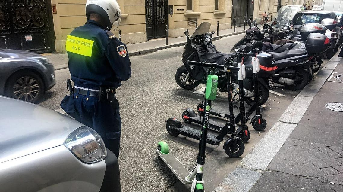 An official from the Mayor of Paris' office moves electric scooters from car parking spaces into those for motorcycles on a road in Paris on June 6, 2019. (AFP)