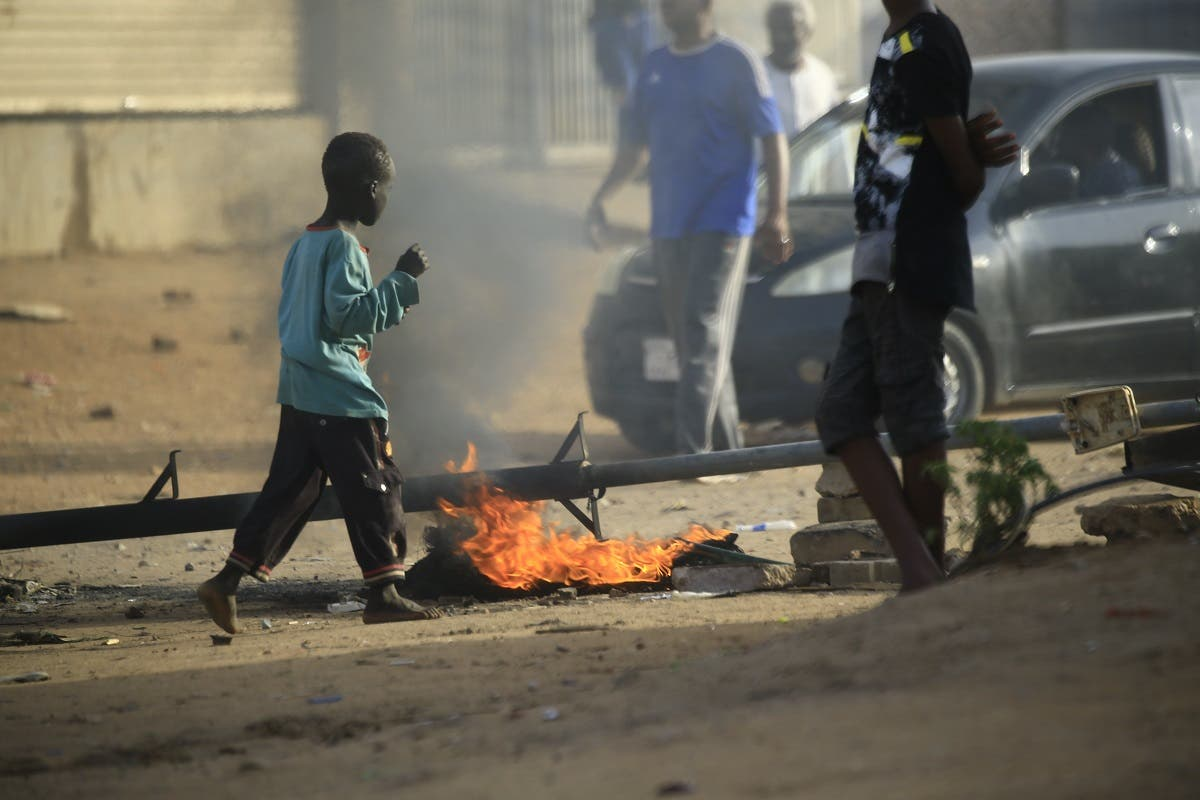 Locals set tires on fire and block a sidestreet leading to their neighborhood in the Sudanese capital Khartoum to stop military vehicles from driving through the area on June 4, 2019. (AFP)