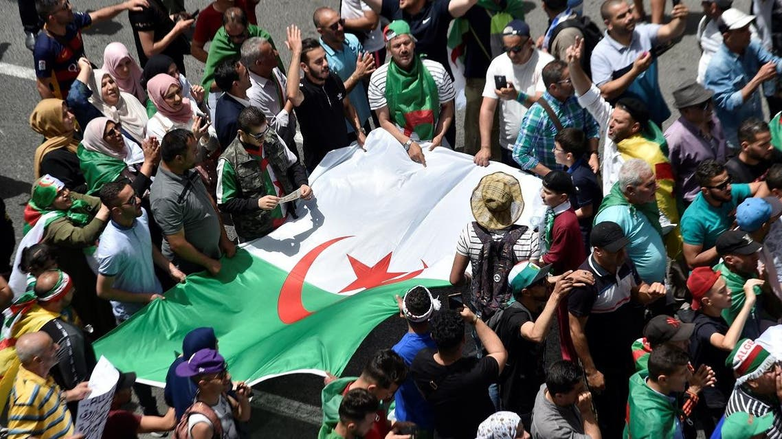 Algerian protesters hold the national flag as they demonstrate in the capital Algiers on June 7, 2019. (AFP)