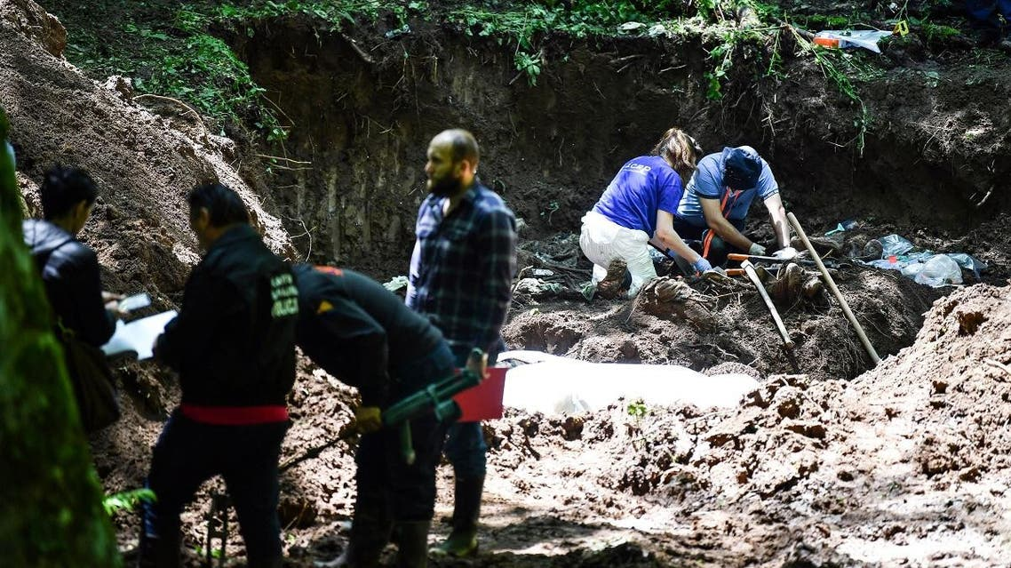 Bosnian workers along side members of the International Committee for Missing Persons (ICMP) work on a newly discovered mass grave on Mt. Igman, near Sarajevo, on June 6, 2019. (AFP)